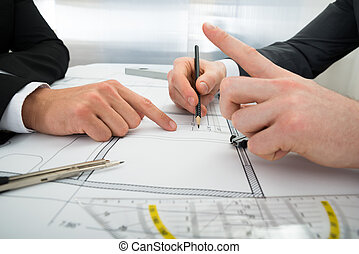 Close-up Of Two Architects Working On Blueprint - Close-up...