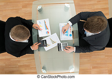 Businessmen With Pen And Calculator Analyzing Graph -...