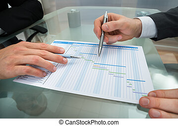 Two Businessmen Making Gantt Diagram - Close-up Of Two...