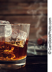 Whiskey and cigar on wooden background close up Vitage toned...