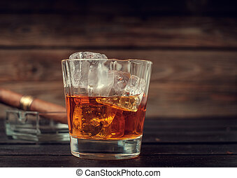 Glass of whiskey with ice and cigar on a wooden background...