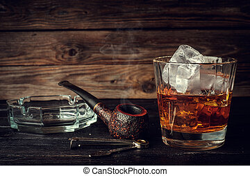 Glass of whiskey with ice and pipe on a wooden background....