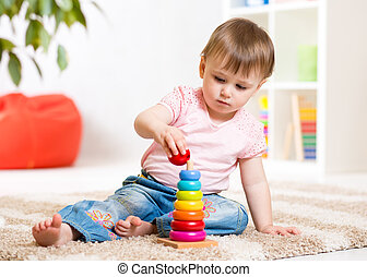 Child girl playing with toy at home