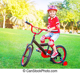 Cute little boy riding a bike in the park in bright sunny...