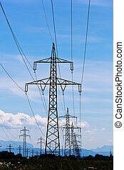 power line - a high-voltage pylons for electricity against a...