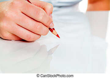 hand with red pencil - a hand holding a red pen symbolic...