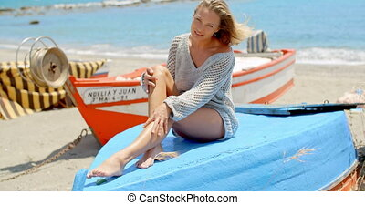 Woman in Sweater Sitting on Blue Platform at Beach - Full...