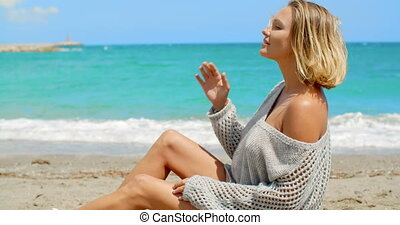 Woman Wearing Grey Sweater Sitting on Sandy Beach - Blond...