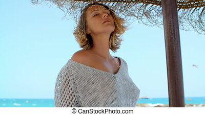 Woman in Grey Sweater in Shade of Beach Umbrella - Waist Up...