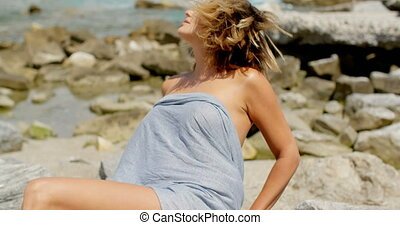 Woman Wrapped in Grey Fabric at Rocky Shoreline - Smiling...