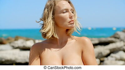 Nude Woman Covering Breasts with Hands by Ocean - Nude Blond...