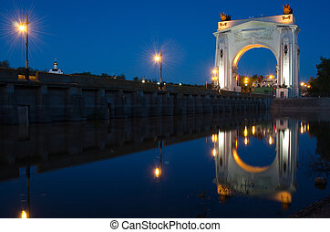 Evening view, with reflection on water arch, to first lock of Volga-Don Canal named after VI Lenina, Volgograd