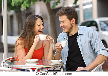 Couple or friends talking and drinking in a restaurant -...