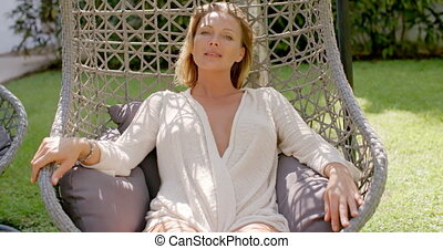 Woman Relaxing in Outdoor Hanging Chair in Garden - Blond...