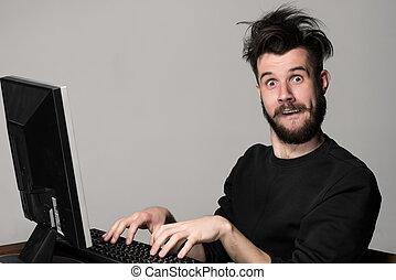 Funny and crazy man using a computer on gray background mans...