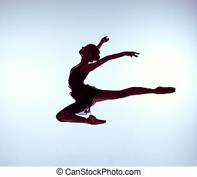Beautiful young ballet dancer jumping on a gray background....