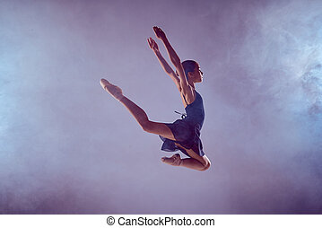 Beautiful young ballet dancer jumping on a lilac background....