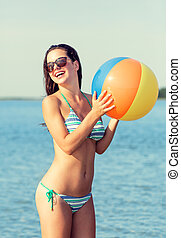 smiling teenage girl sunglasses with ball on beach - sea,...