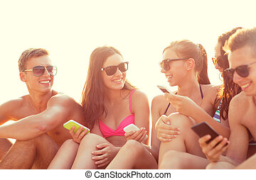 group of smiling friends with smartphones on beach -...