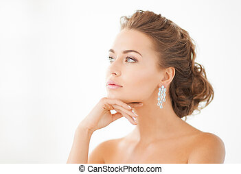 woman wearing shiny diamond earrings - close up of beautiful...
