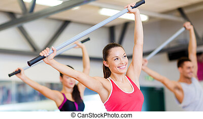 group of smiling people working out with barbells - fitness,...