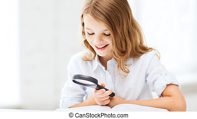girl reading book with magnifier at school - education and...