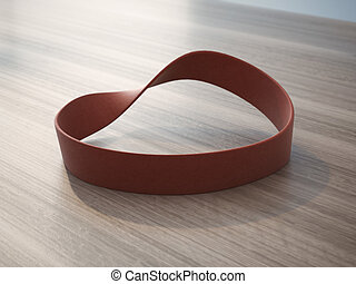 Twisted red rubber wrist band on wooden table