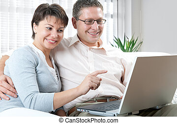 couple on laptop - happy couple using laptop at home