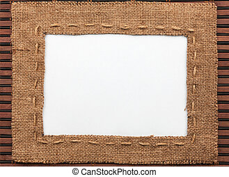 Frame made of burlap with white background lying on a bamboo...