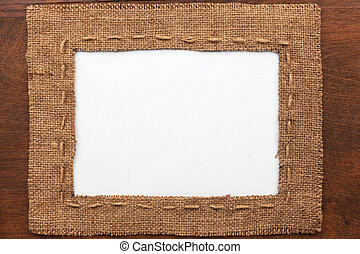 Frame made of burlap with white background lying on a wooden...