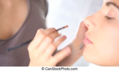 makeup artist applying eyeshadow on eyelid using makeup...