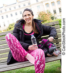 fitness break - young woman sitting on a bench in a park