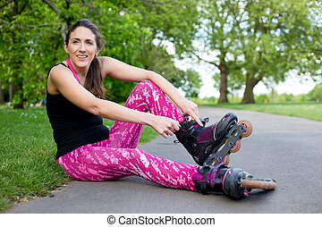 roller skating - young woman fastening her rollerblades