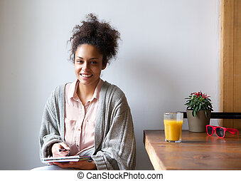 Smiling woman sitting at home with pen and paper - Portrait...