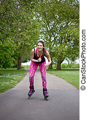 roller skating - young woman rollerblading in the park
