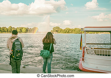 Alster Lake in Hamburg Germany with boat and two tourists -...