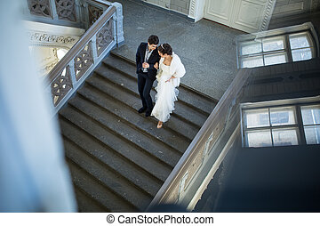Fancy wedding couple holding hands walking the stairs down -...