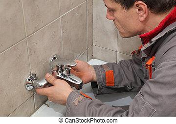 Plumber works in a bathroom