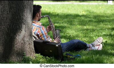 A young man plays the saxophone - In warm sunny day the guy...