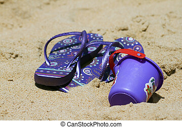 Children's sandy toys and flip-flop on a beautiful beach. India Goa