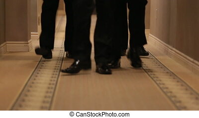 Feet of man in black shoes - Four pairs of mens feet walking...