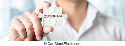 Businessman Shows Puzzle Piece with Tutorial Text - Close up...