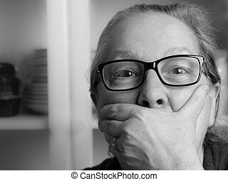 Amazed middle aged woman with hand in front of mouth -...
