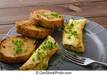 French omelette with chives, fresh herbs and garlic toast