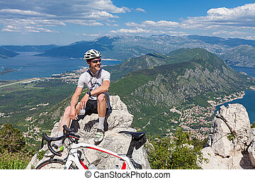 Cyclist on the top of a hill sitting on a background of the...