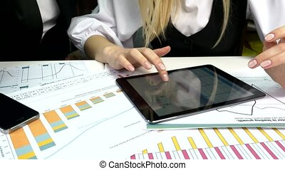 Business peoples developing a business project and analyzing market data information on a modern digital tablet computer