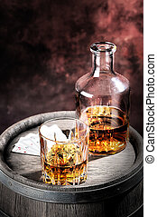 Faceted glass and dusty decanter of brandy on a wooden...