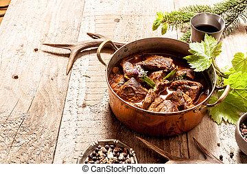 Venison Goulash in Copper Pot on Wooden Surface - Venison...