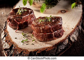 Venison Steak Filets Served on Rustic Wood Plank - Close Up...