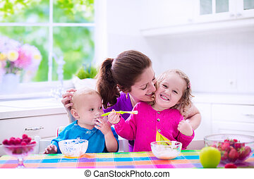 Mother and children having breakfast - Family having...